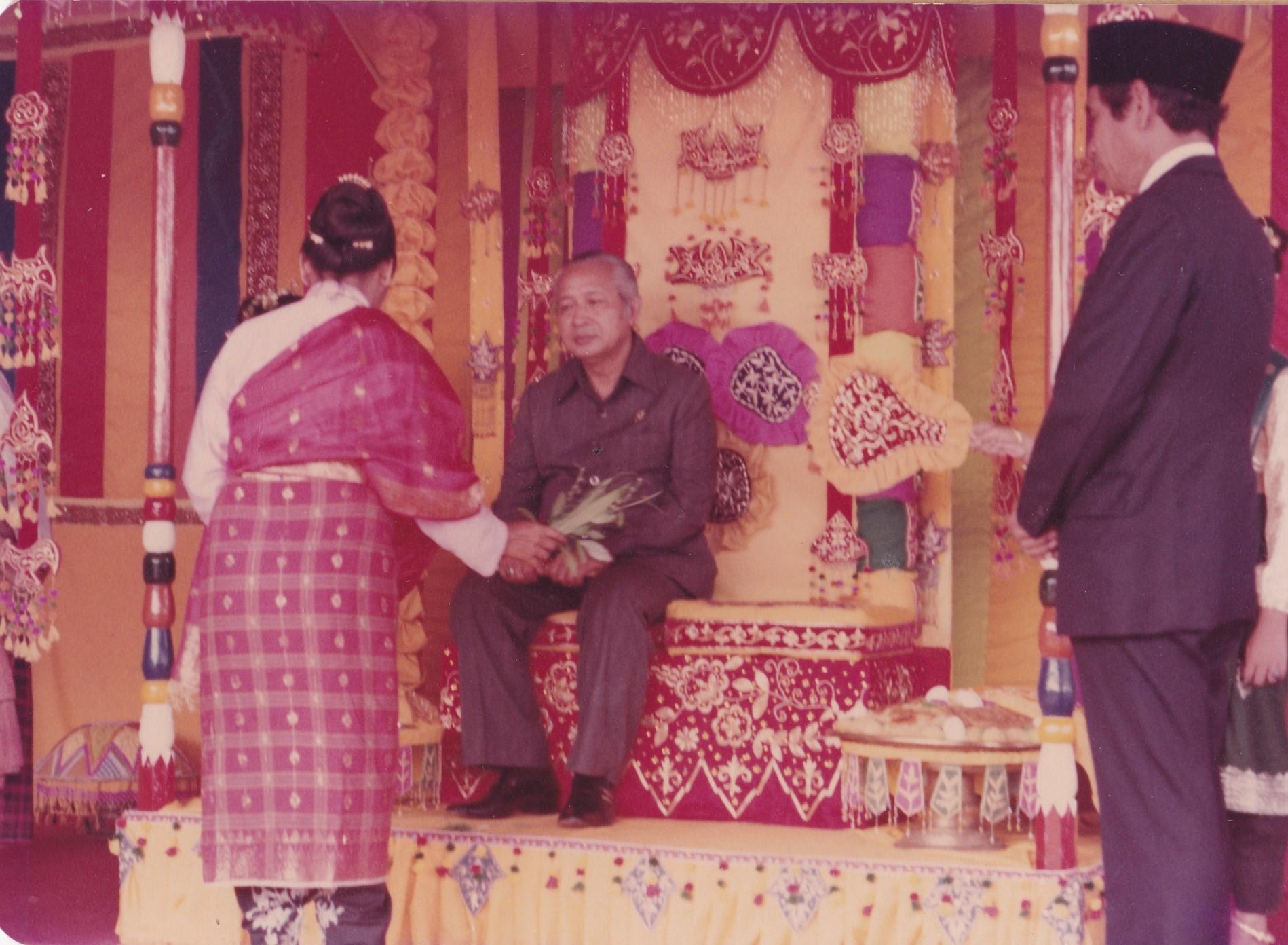 (Keterangan Photo:  Pak Harto, sedang duduk sejenak di kusi adat untuk di Peusejuk. Sesaat tiba di Bandara Malikulsaleh, sebelum meresmikan PT LNG ARun-Aceh 19 Desember 1978, Lhokseumawe, Aceh. Berdiri di kanan: Gubernur Aceh saat itu, Prof DR Madjid Ibrahim / Photo: Dok Pribadi penulis)
