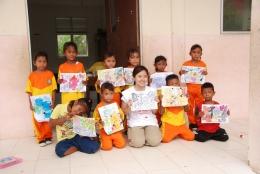 Para pelajar TK menunjukkan hasil karya mewarnai mereka.