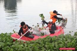Viera (17) --- tengah --- sedang mengumpulkan eceng gondok dan sampah yang diangkat dari perairan Situ Tujuh Muara. (Foto: Gapey Sandy)