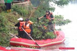 Putri (kanan) menurunkan muatan eceng gondok ke pinggir situ dari atas perahu karet. (Foto: Gapey Sandy)