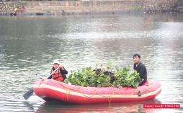 Viera (17) tengah mendayung perahu karet penuh bermuatan eceng gondok siap buang. (Foto: Gapey Sandy)