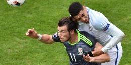 PHILIPPE HUGUEN/AFP Bek Inggris, Chris Smalling (kanan), berduel dengan penyerang Wales, Gareth Bale