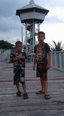 Dua orang anak sedang berpose dengan latar Menara Pandang ke Pantai Ulee Lheu (foto dok pri).