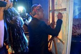 Ketua Komunitas BIOTIC SADULUR, Ahep, sedang menandatangani Lukisan karya Bahar Malaka yang akan diserahkan kepada Pemerintah Kabupaten Sumedang. (Sumber foto: Biotic Sadulur)