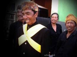 Pak Tomo, Dukun Adat memakai slempang kuning sebagai tanda sesepuh desa.