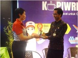 Kepala Bidang Perindustrian Dinas Perdagangan dan Perindutrian Provinsi Bali, I Gede Wayan Suamba, SE menerima plakat dari Kepala JNE Denpasar, Ibu Alit Septiniwati (Sumber: dokumen pribadi)