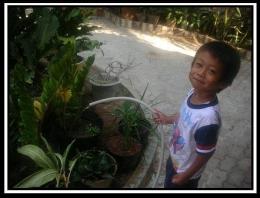 Keponakan menyirami tanaman. Photo by Ari