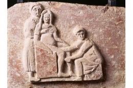 Sebuah relief abad kedua Masehi di makam bidan Romawi Scribonia Attica menggambarkannya di tempat kerja. /Foto : Getty Images