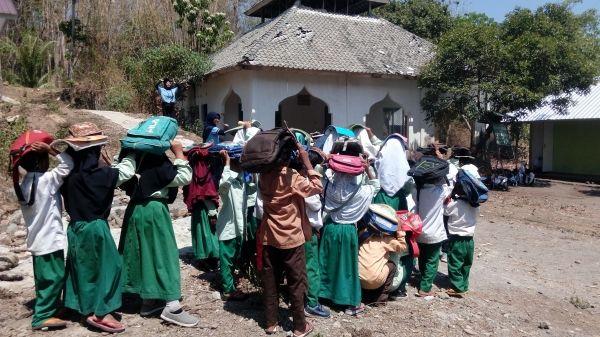 Para siswa saat memperagakan cara melindungi diri dari runtuhan tanah longsor (dokpri)