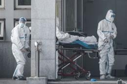 Petugas medis membawa seorang pasien yang diduga terinfeksi virus misterius mirip SARS, ke rumah sakit Jinyintan, di Kota Wuhan, China, Sabtu (18/1/2020). Virus misterius mirip pneumonia telah menjangkiti puluhan orang dan menelan korban jiwa kedua di China, menurut pemerintah setempat.(AFP/STR/CHINA OUT via KOMPAS.com)