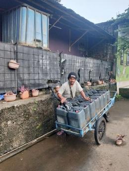 Mang Asep mengisi air di pusat penampungan untuk dijajakan berkeliling sejumlah perumahan. (foto: dok. pribadi)