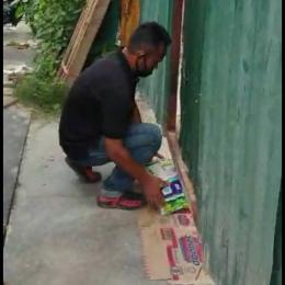 Jamal ketika menyerahkan beras melalui celah bawah pintu // foto:IKMA