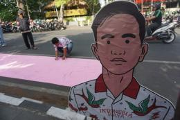 Warga membubuhkan tanda tangan dukungan terhadap putra sulung Presiden Jokowi, Gibran Rakabuming Raka maju Pilkada Solo 2020 di Jalan Bhayangkara Solo, Jawa Tengah, Minggu (3/11/2019). (Foto: KOMPAS.com/LABIB ZAMANI)