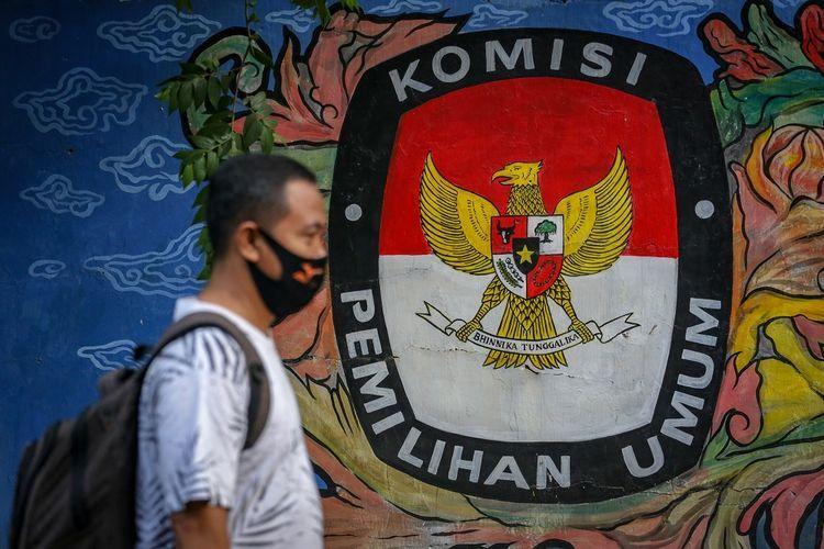 Warga melintas di depan mural bertema pemilihan umum di kawasan Pasar Anyar, Kota Tangerang, Banten, Kamis (7/5/2020). Presiden Joko Widodo menunda pemungutan suara Pemilihan Kepala Daerah (Pilkada) 2020 hingga Desember 2020 akibat wabah COVID-19. ANTARA FOTO/Fauzan/aww.(ANTARA FOTO/FAUZAN via KOMPAS.com)