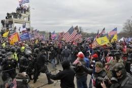 Massa pendukung Presiden Amerika Serikat (AS) Donald Trump bentrok dengan pasukan keamanan saat mereka menerobos masuk Gedung Capitol, Washington DC, paa 6 Januari 2021. Bentrokan terjadi setelah massa berusaha menghentikan kemenangan Joe Biden.(AFP PHOTO/JOSEPH PREZIOSO via kompas.com)