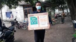 Salah satu Mahasiswa KKN Kelompok 58 UM Jember sekaligus Koordinator Desa Moh Syamsi Qurtubi membawa kardus berisi buku di dusun Selatan Ledeng Desa Sumber Pinang. Selasa (02/04/2021).