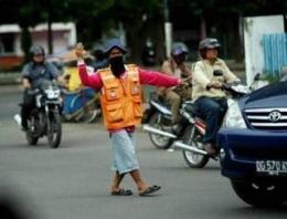 Seorang Tukang Parkir Yang Mengarahkan Kendaraan. Sumber Hipwee.com