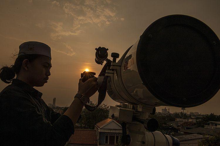 Seorang petugas masjid mencari posisi hilal menggunakan teropong. Foto: kompas.com.