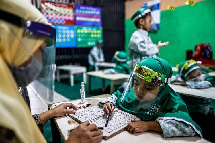 Guru menggunakan masker dan pelindung wajah saat menerangkan pelajaran dalam kelas tatap muka di TK An-Nuur, Jakarta Selatan, Selasa (4/8/2020). Uji coba pembelajaran tatap muka ini berlangsung dengan menjalankan protokol kesehatan Covid-19.(KOMPAS.com/GARRY LOTULUNG)