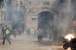 Warga Palestina melarikan diri ketika polisi menembakkan granat kejut selama bentrokan di kompleks Masjid Al-Aqsa | Foto dari Reuters/Ammar Awad