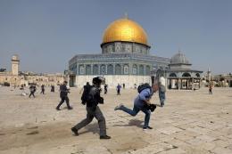 Seorang anggota polisi Israel mengejar seorang warga Palestina di kompleks Masjid Al-Aqsa pada 10 Mei 2021 | Foto dari Reuters/Ammar Awad