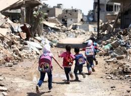Para murid berlari melewati bangunan yang rusak di kota Damaskus, Suriah pada 30 April 2016   Foto diambil dari The Atlantic