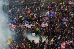 Pendukung Presiden Donald Trump bentrok dengan pasukan keamanan di Gedung Capitol, Washington DC. (Foto: AFP PHOTO/ROBERTO SCHMIDT via KOMPAS.COM)