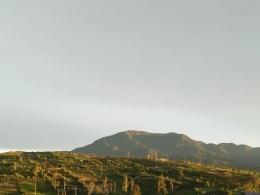 Bukit dan lahan pertanian dengan latar belakang gunung