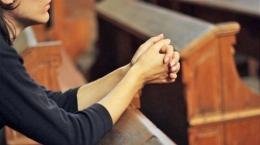 Seorang perempuan tengah berdoa di dalam Gereja. Foto: skkksurakarta.sch.id.