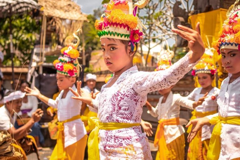 Ilustrasi anak kecil menari dan memakai baju tradisional   Pexels/Artem Beliaikin