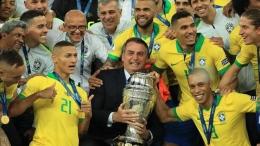 Jair Bolsonaro (Presiden Brasil) bersama trofi Copa America 2019 dan Skuad Timnas Brasil (Goal.com)