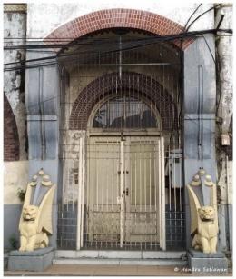 Singa sang penjaga dan bentukan lengkung bata merah sebagai ciri khas bangunan (foto: dok. pribadi)