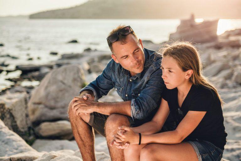 Sumber: https://takaitu.id/ketika-menjadi-single-parent-di-usia-muda/father-and-daughter-sitting-on-a-rocky-beach-and-talking/
