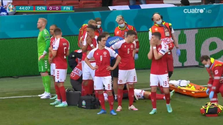 Pemain Denmark menutupi badan Christian Eriksen yang tengah mendapatkan penanganan tim medis. Eriksen mendadak kolaps saat Denmark bersua Finlandia di laga Grup B Euro 2020, Sabtu (12/6) malam. Kini, kondisinay dikabarkan membaik/Foto: Marca