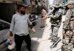 Aparat keamanan India menindak warga yang melanggar ketentuam lockdown, sumber foto : Reuters via kumparan.com 26/3/2020