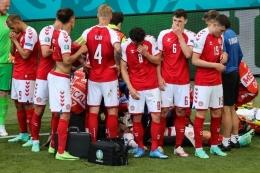Para pemain Denmark mengelilingi Christian Eriksen yang tiba-tiba kolaps di tengah pertandingan melawan Finlandia. Laga Denmark vs Finlandia merupakan pembuka Grup B Euro 2020 yang digelar di Stadion Parken, Sabtu (13/6/2021). (AFP/WOLFGANG RATTAY via KOMPAS.com)