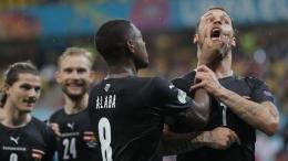 Kapten Timnas Austria David Alaba membungkam mulut Marko Arnautovic usai mengucapkan ungkapan rasis dalam selebrasi gol yang dicetaknya. Dalam laga itu Austria menang 3-1 lawan Makedonia Utara (detik.com/ AP/ Robert Ghement).