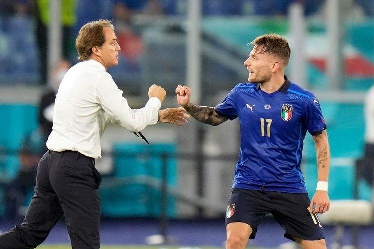 Pelatih Timnas Italia, Roberto Mancini, memberi selamat kepada Ciro Imobile setelah ia mencetak gol ketiga Azzurri pada laga Grup A Euro 2020 di Estadio Olimpico pada Kamis (17/6/2021) dini hari WIB. (Foto: AFP/ALESSANDRA TARANTINO via Kompas.com)