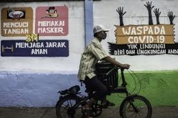 Warga melintas di depan mural yang berisi pesan waspada penyebaran virus Corona di Petamburan, Jakarta, Rabu (16/9/2020). Mural tersebut dibuat untuk mengingatkan masyarakat agar menerapkan protokol kesehatan saat beraktivitas karena masih tingginya angka kasus COVID-19 secara nasional. ANTARA FOTO/Aprillio Akbar/aww.(ANTARA FOTO/Aprillio Akbar)