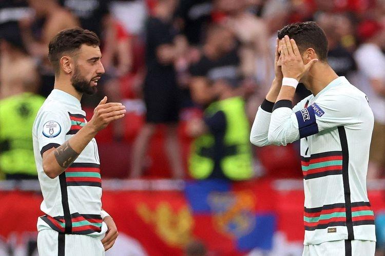 Bruno Fernandes (kiri) bersama rekan setimnya, Cristiano Ronaldo (kanan) pada laga pembuka Grup F Euro 2020 Hongaria vs Portuga di Stadion Puskas Arena, Selasa (15/6/2021) malam WIB.|. Sumber foto: AFP/BERNADETT SZABO via Kompas.com