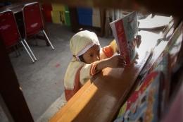 seorang anak sedang mengembalikan buku bacaannya (sumber : kompas)