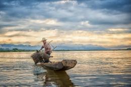 Seorang nelayan sedang memasang perangkap ikan (Pixabay.com)