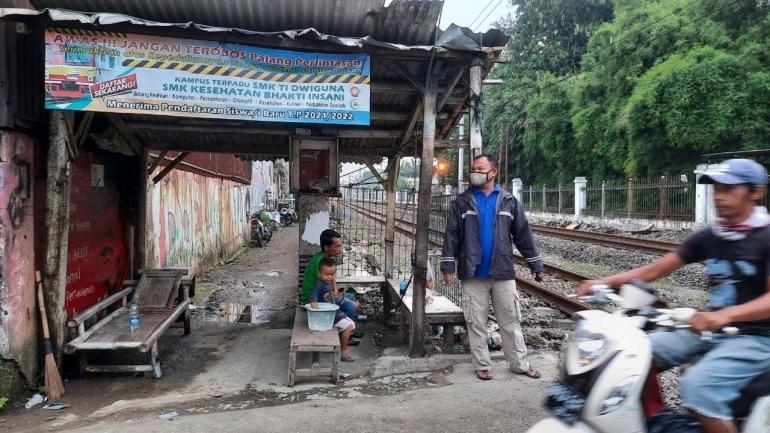 (Foto: Yosi Avelina)Burhan sedang menjaga pintu perlintasan kereta di gang Haji Dul, Rabu (30/6), Depok.