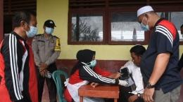 Kepala Desa Belaras (kopiah putih), Kepala Pustu Belaras (baju kaos lengan panjang), dan babinkatibmas mengawasi kegiatan vaksinasi. (foto : Elvidayan