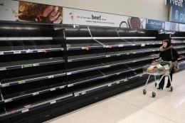 Seorang pembelanja berjalan melewati rak-rak makanan kosong di tengah pandemi coronavirus COVID-19 yang baru, di Manchester, Inggris utara pada 20 Maret 2020. (AFP/Oli SCARFF)