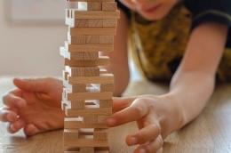 Seorang anak memilih balok agar bangunan tinggi Jenga tidak roboh. Sumber : Pixabay.