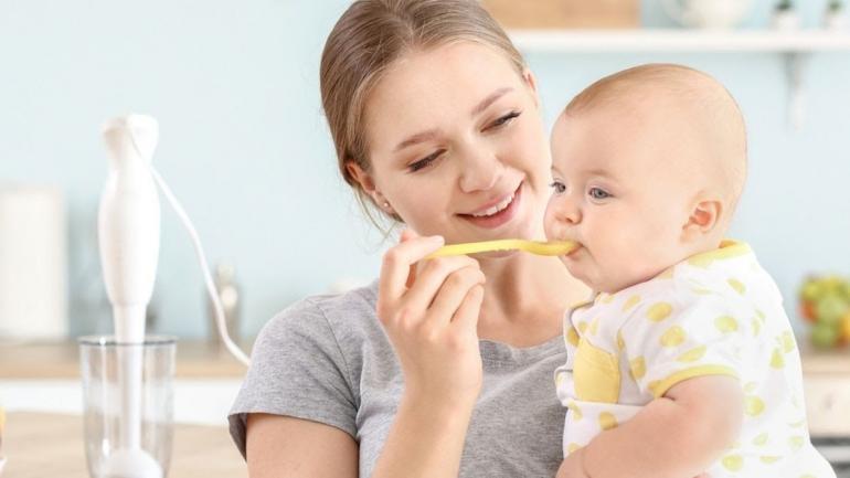 Perbedaan Menu MPASI pada Bayi Zaman Dulu, Kini, dan Nanti (foto seorang ibu memberikan MPASI bubur pada bayinya via klikdokter.com)