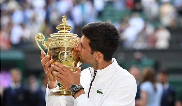 Novak Djokovics mencium trophy Wimbledon, 14 Juli 2019(beritasatu.com)