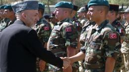 Afghan President Hamid Karzai (L) shakes hands with a Turkish soldier of the NATO-led International Security Assistance Force (ISAF) during a transfer of command ceremony at the ISAF headquarters in Kabul, Oct. 5, 2006. - SHAH MARAI/AFP via Getty Images