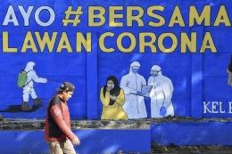 Seorang warga yang tidak mengenakan masker melintas, di depan mural yang berisi pesan waspada penyebaran virus Corona di kawasan Tebet, Jakarta, Selasa (8/9/2020). ANTARA FOTO/M Risyal Hidayat dipublikasikan Kompas.com